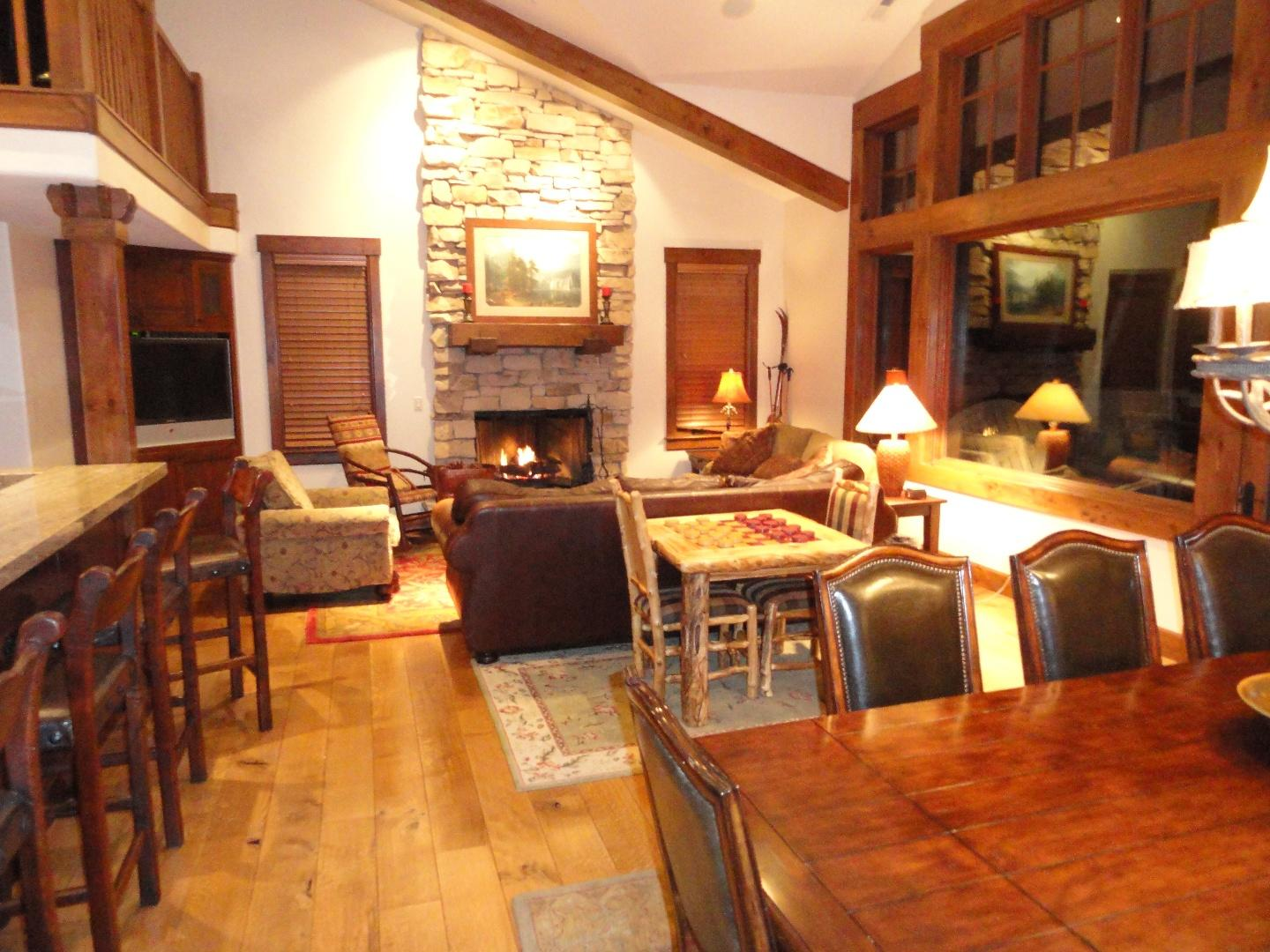 Great room with vaulted ceiling and fireplace Slide-3